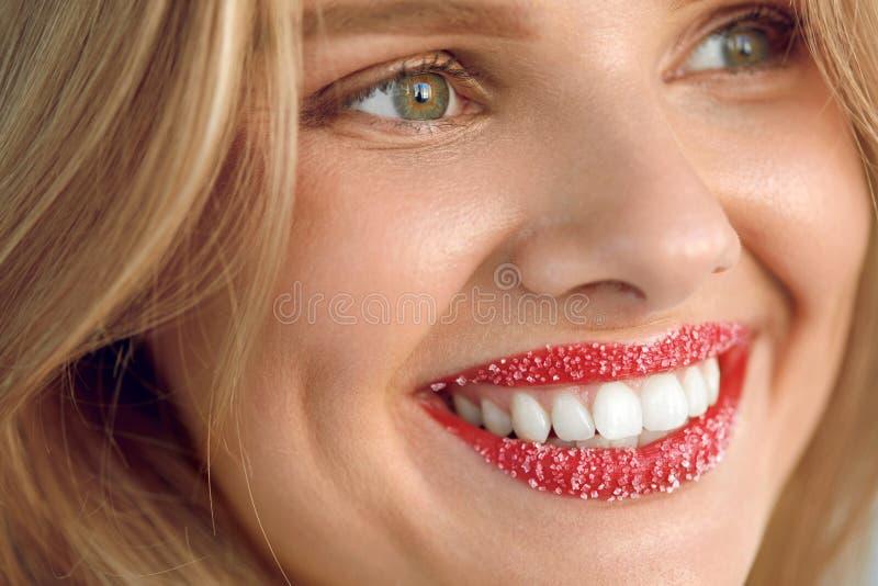 Η γυναίκα με το όμορφο χαμόγελο, χείλι ζάχαρης τρίβει στα χείλια Πρόσωπο ομορφιάς στοκ φωτογραφία