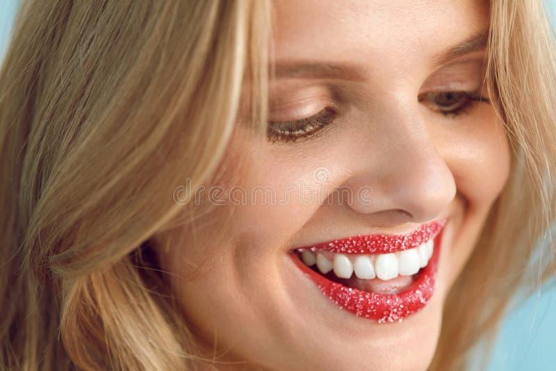 Η γυναίκα με το όμορφο χαμόγελο, χείλι ζάχαρης τρίβει στα χείλια Πρόσωπο ομορφιάς στοκ εικόνα με δικαίωμα ελεύθερης χρήσης