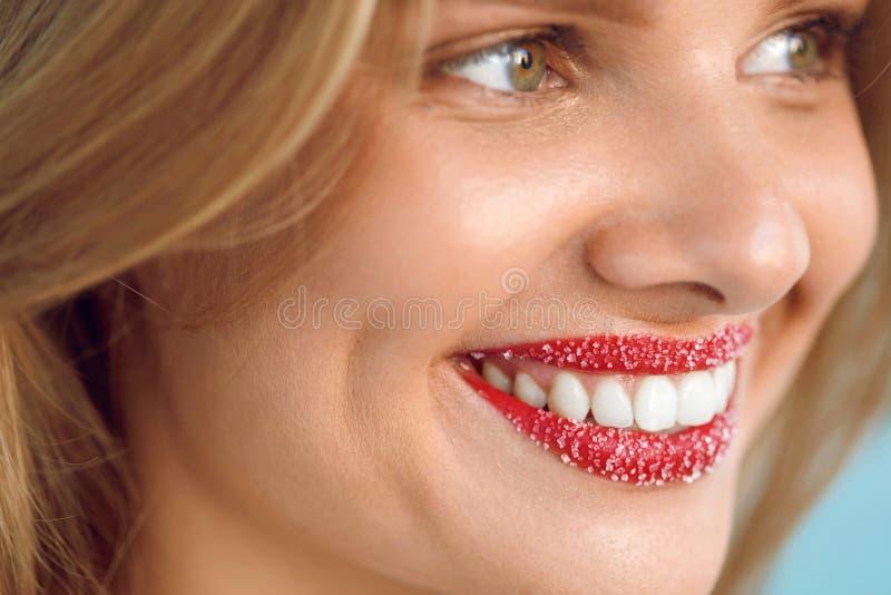 Η γυναίκα με το όμορφο χαμόγελο, χείλι ζάχαρης τρίβει στα χείλια Πρόσωπο ομορφιάς στοκ φωτογραφία με δικαίωμα ελεύθερης χρήσης