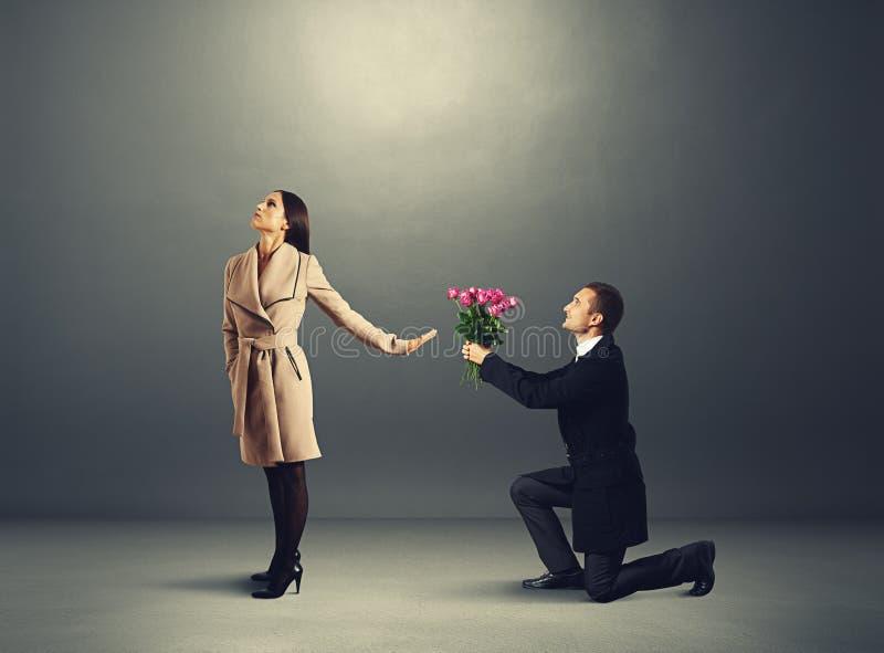 Η γυναίκα μην εξετάζοντας τον άνδρα με τα λουλούδια στοκ φωτογραφία με δικαίωμα ελεύθερης χρήσης