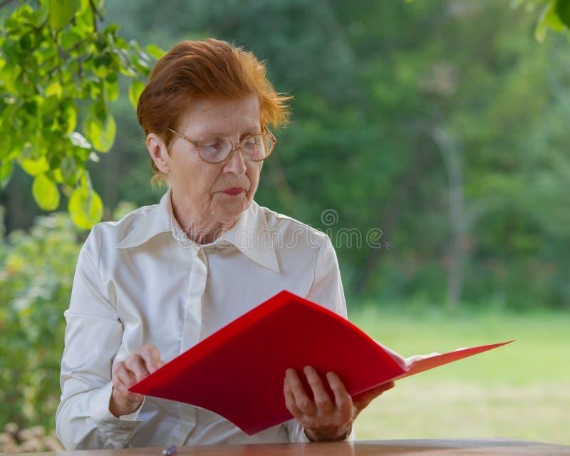 Η γυναίκα μιας επιχειρηματία στην ηλικία εξετάζει τα έγγραφα στοκ φωτογραφίες