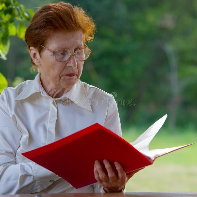 Η γυναίκα μιας επιχειρηματία στην ηλικία εξετάζει τα έγγραφα στοκ φωτογραφίες με δικαίωμα ελεύθερης χρήσης