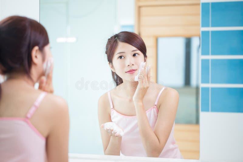 Η γυναίκα ομορφιάς καθαρίζει το πρόσωπό της στοκ φωτογραφία με δικαίωμα ελεύθερης χρήσης