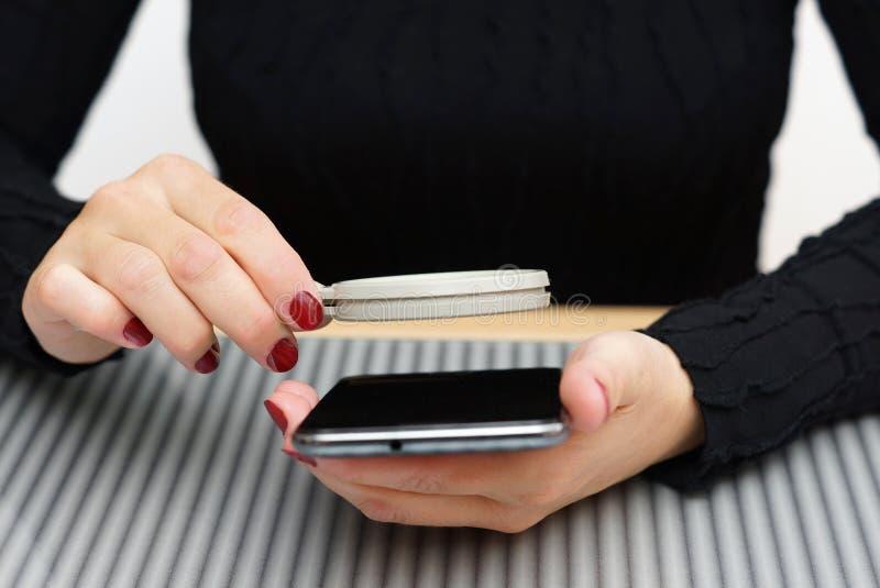 Η γυναίκα λοξοτομεί το διαβασμένο μικρό κείμενο στο κινητό τηλέφωνο χωρίς ενίσχυση gl στοκ φωτογραφία με δικαίωμα ελεύθερης χρήσης