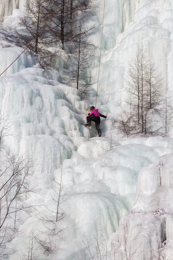Η γυναίκα ορειβατών πάγου ανέρχεται έναν παγωμένο καταρράκτη στοκ εικόνα