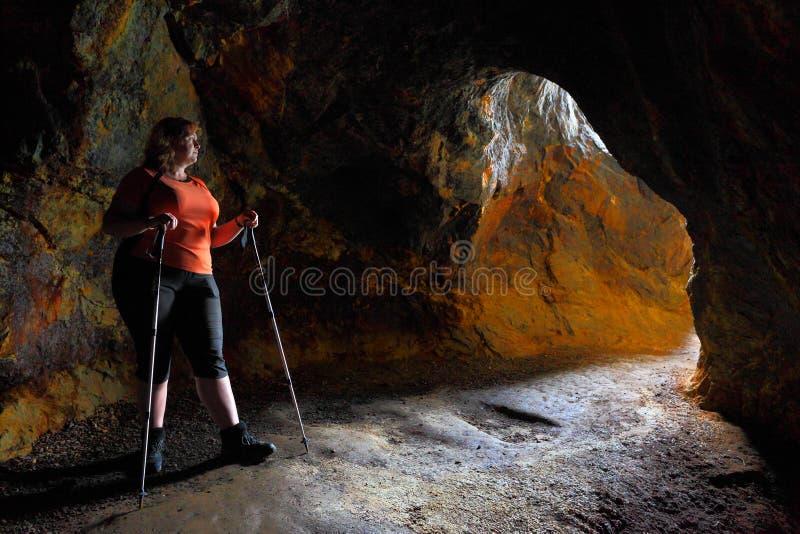 Η γυναίκα οδοιπόρων εξερευνά το αρχαίο υπόγειο ορυχείο στοκ εικόνα με δικαίωμα ελεύθερης χρήσης