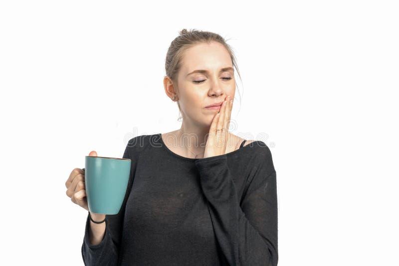 Η γυναίκα πίνει τον καυτό καφέ και είναι ευαίσθητη στη θερμότητα στοκ φωτογραφία