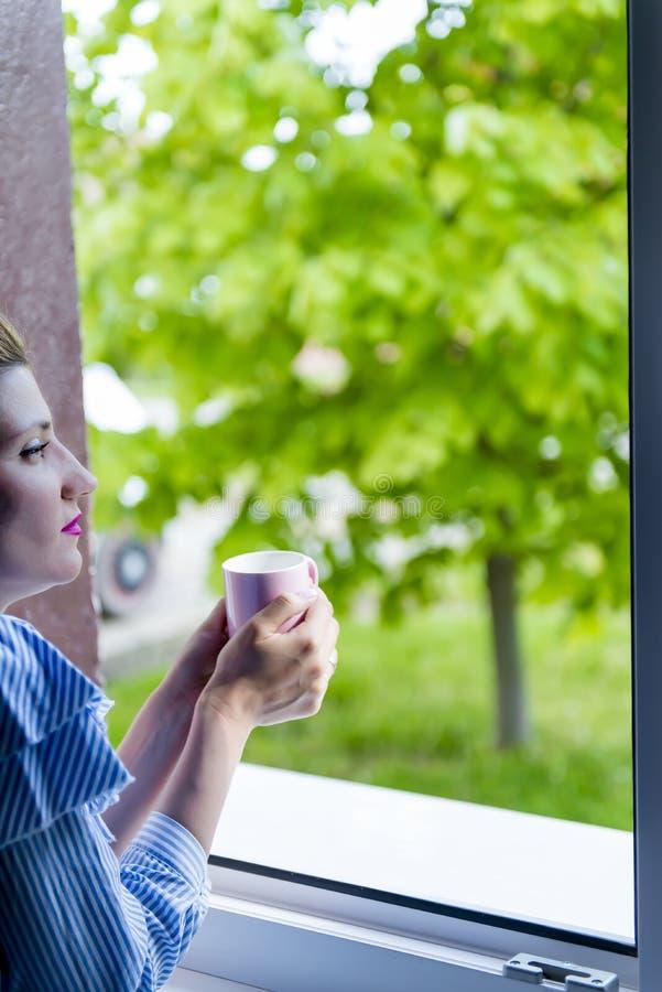 Η γυναίκα πίνει τον καφέ στοκ φωτογραφίες