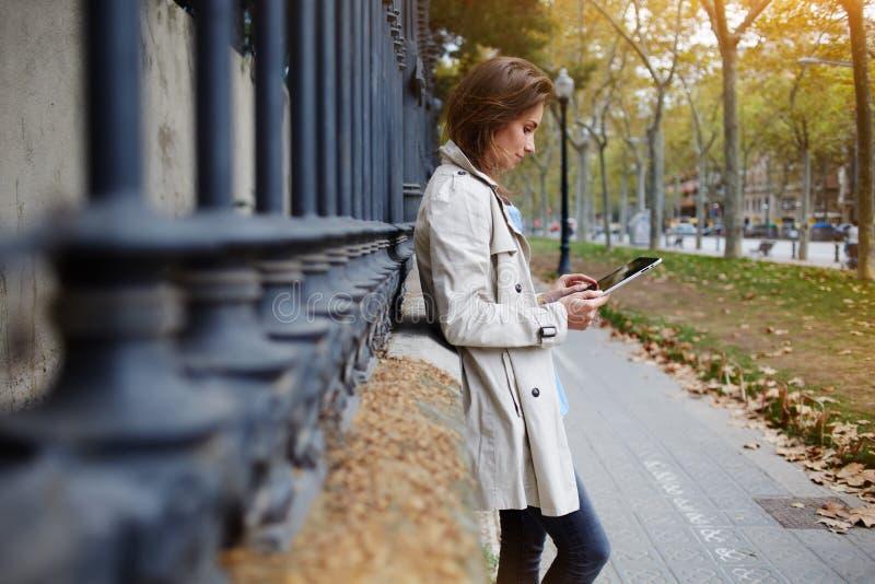 Η γυναίκα παίζει τα παιχνίδια στην ψηφιακή ταμπλέτα, ενώ περιμένει το φίλο υπαίθριο στοκ φωτογραφία με δικαίωμα ελεύθερης χρήσης