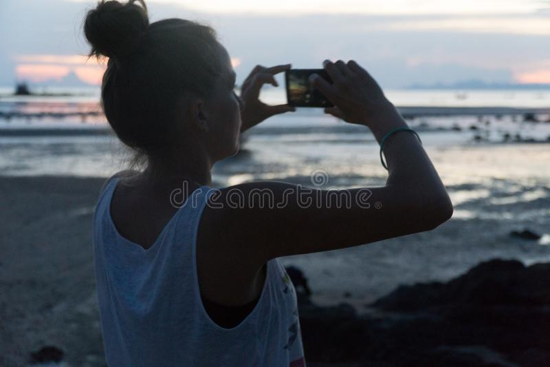 Η γυναίκα παίρνει ένα ηλιοβασίλεμα επάνω από τη θάλασσα σε μια τηλεφωνική κάμερα στοκ εικόνες