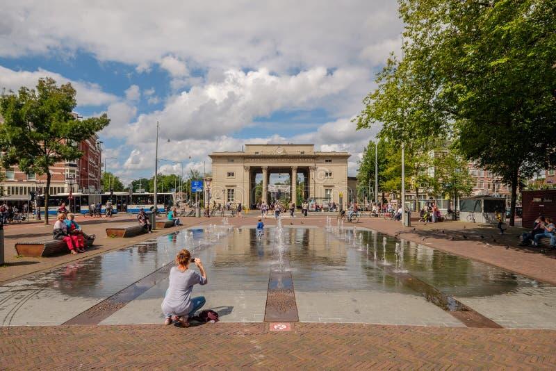 Η γυναίκα παίρνει μια εικόνα του παιδιού της που παίζει στην πηγή σε ένα τετράγωνο μπροστά από μια ιστορική πύλη πόλεων στο Άμστε στοκ εικόνες