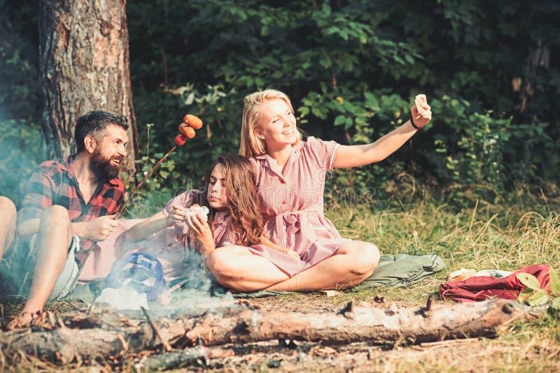 Η γυναίκα παίρνει τη φωτογραφία ή το βίντεο με το smartphone στους δασικούς φίλους παίρνει selfie με τα λουκάνικα στη φωτιά Φίλος στοκ φωτογραφία με δικαίωμα ελεύθερης χρήσης