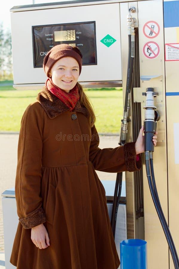 η γυναίκα παίρνει το πυροβόλο όπλο για τον ανεφοδιασμό σε καύσιμα του αυτοκινήτου φυσικού αερίου στοκ εικόνες