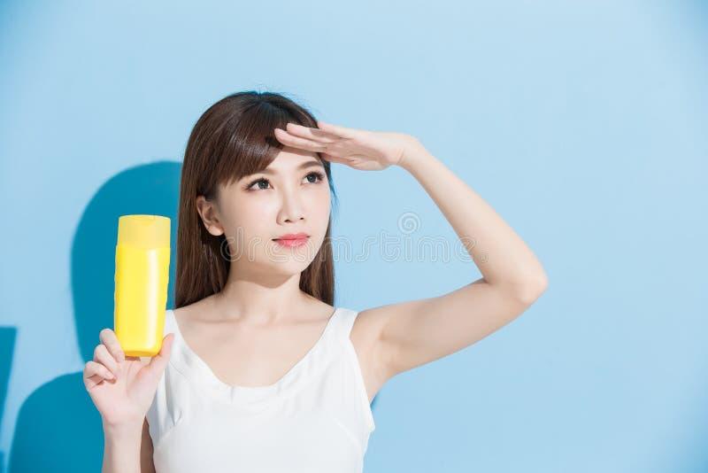 Η γυναίκα παίρνει sunscreen στοκ φωτογραφίες