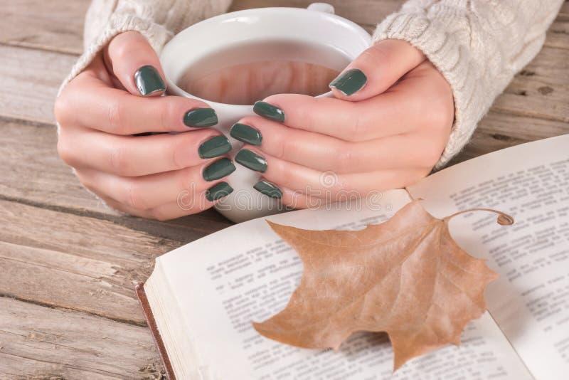 Η γυναίκα παραδίδει το πουλόβερ με το μανικιούρ χρώματος ελιών κρατά το φλυτζάνι του τσαγιού και του ανοικτού βιβλίου στοκ εικόνες