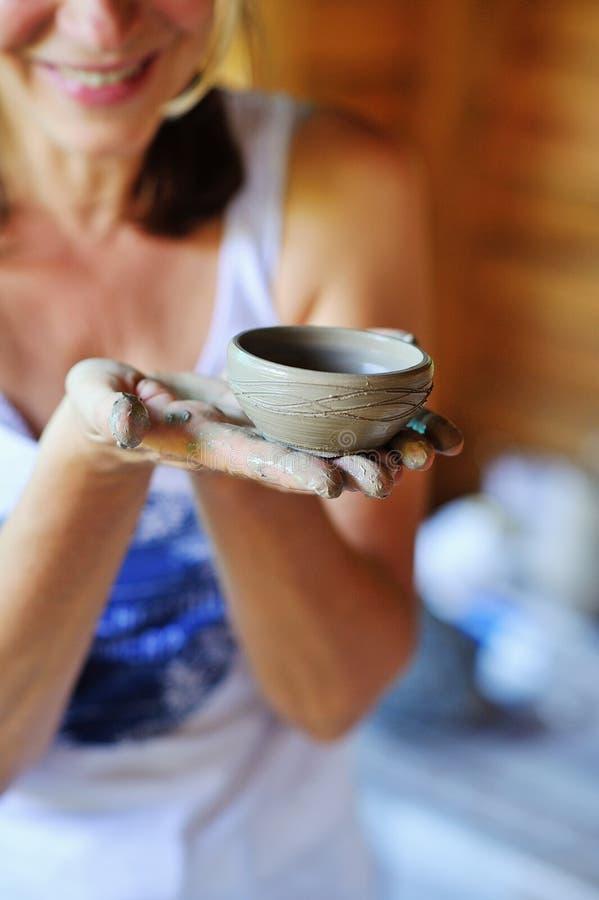 Η γυναίκα παραδίδει τον άργιλο κρατώντας το χειροποίητο δοχείο στοκ εικόνες