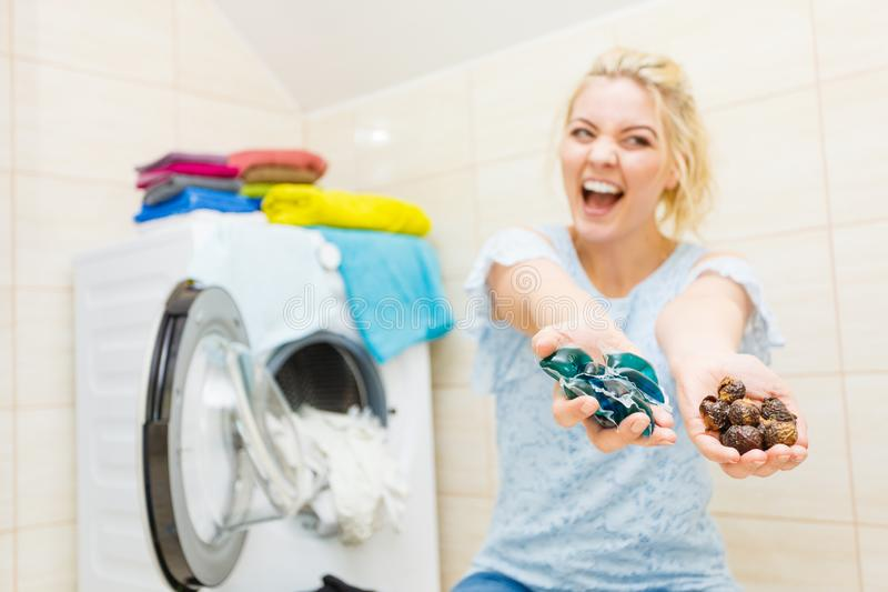 Η γυναίκα παρουσιάζει απορρυπαντικό καρυδιών σαπουνιών και λοβών πηκτωμάτων στοκ φωτογραφίες