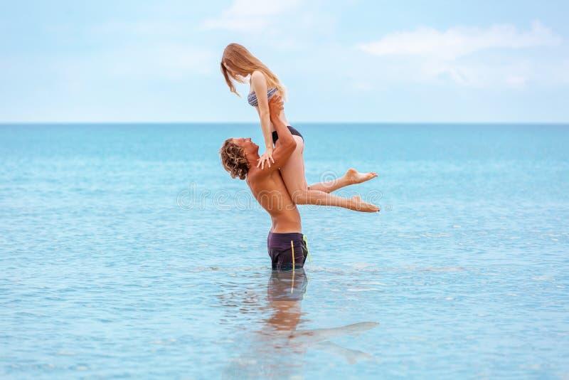Η γυναίκα πηδά στον άνδρα στα όπλα του, που στέκονται στη θάλασσα Και οι δύο είναι στα μαγιό  στοκ εικόνα με δικαίωμα ελεύθερης χρήσης