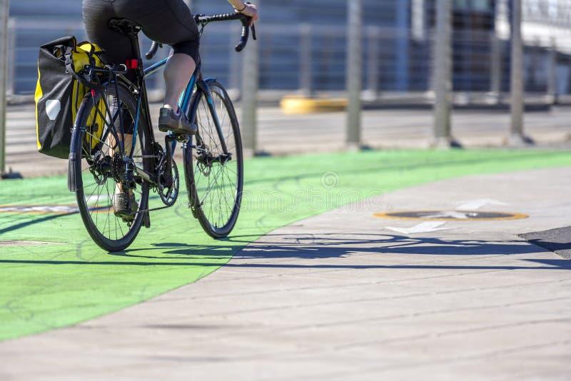 Η γυναίκα ποδηλατών οδηγά ένα οδικό ποδήλατο στην αφιερωμένη πορεία ποδηλάτων στοκ φωτογραφία