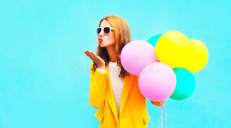 Η γυναίκα πορτρέτου κρατά ότι τα μπαλόνια στέλνουν ένα φιλί αέρα στο κίτρινο παλτό στοκ εικόνες