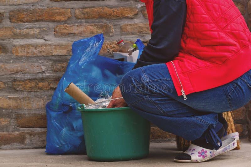 Η γυναίκα που βάζει τα απορρίματα μπορεί μέσα και πλαστική τσάντα στοκ φωτογραφία με δικαίωμα ελεύθερης χρήσης