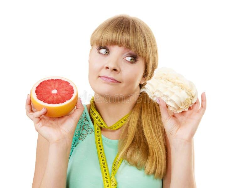 Η γυναίκα που επιλέγει τα φρούτα ή το κέικ κάνει τη διαιτητική επιλογή στοκ εικόνες με δικαίωμα ελεύθερης χρήσης