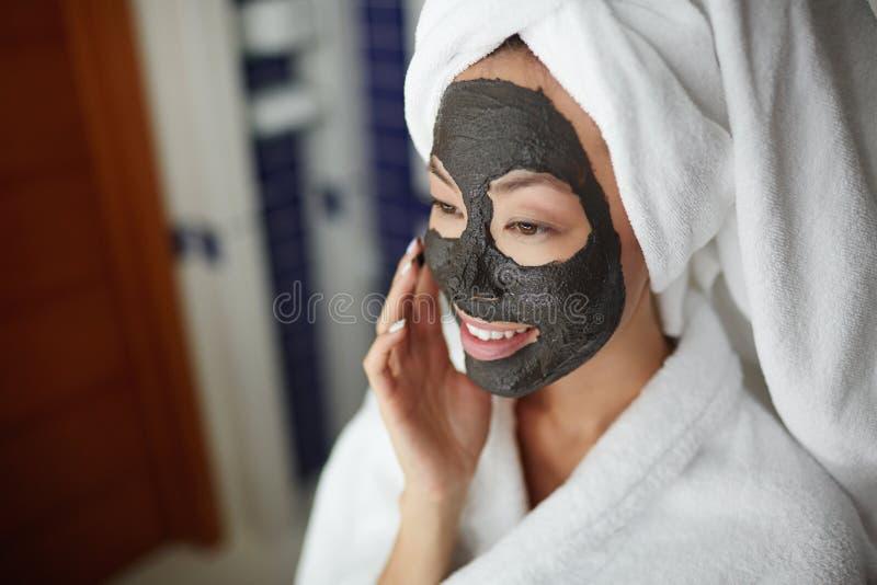 Η γυναίκα που εφαρμόζει τον καθαρισμό προσώπου τρίβει στοκ φωτογραφία με δικαίωμα ελεύθερης χρήσης