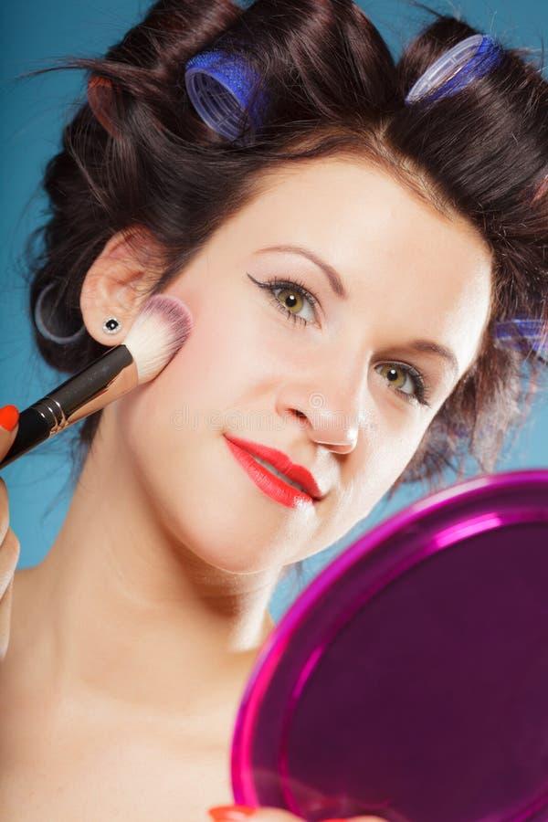 Η γυναίκα που εφαρμόζει το ρουζ κοκκινίζει makeup στοκ εικόνα