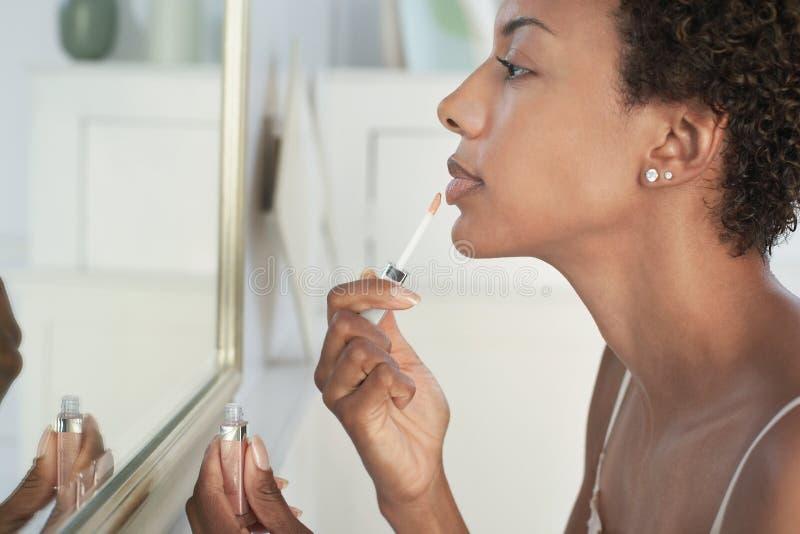 Η γυναίκα που εφαρμόζει το χείλι σχολιάζει στον καθρέφτη στο σπίτι στοκ εικόνα