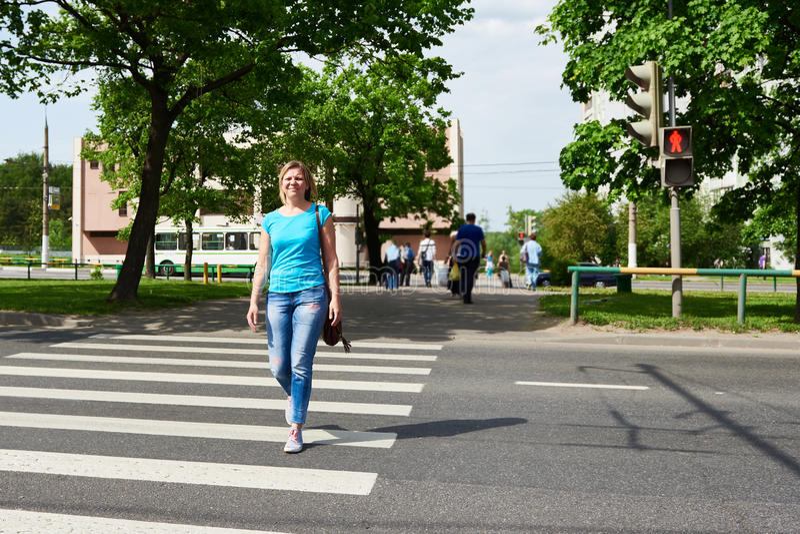 Η γυναίκα που διασχίζει την οδό είναι επικίνδυνη στο κόκκινο φως στοκ εικόνα με δικαίωμα ελεύθερης χρήσης