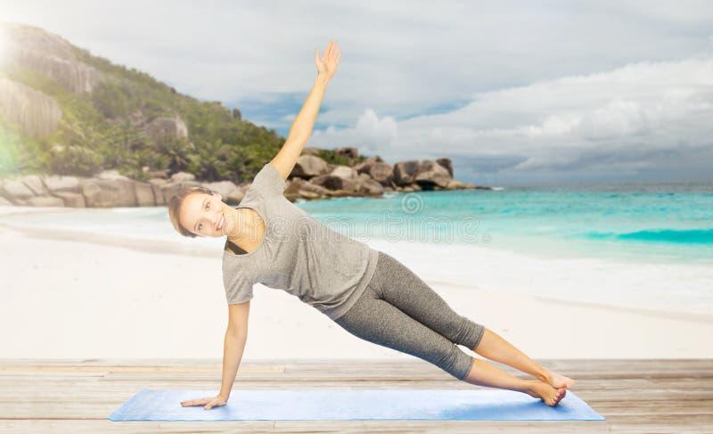 Η γυναίκα που κάνει τη γιόγκα στη δευτερεύουσα σανίδα θέτει στην παραλία στοκ φωτογραφία