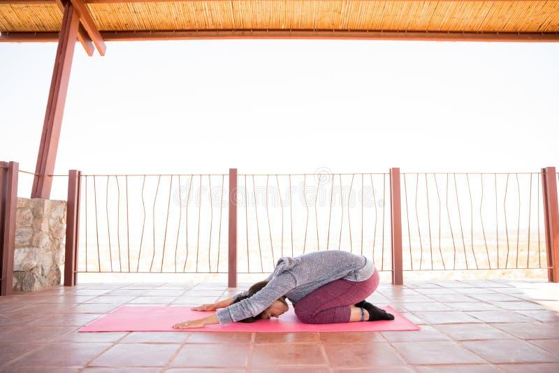 Η γυναίκα που κάνει το παιδί θέτει τη γιόγκα workout στοκ φωτογραφίες