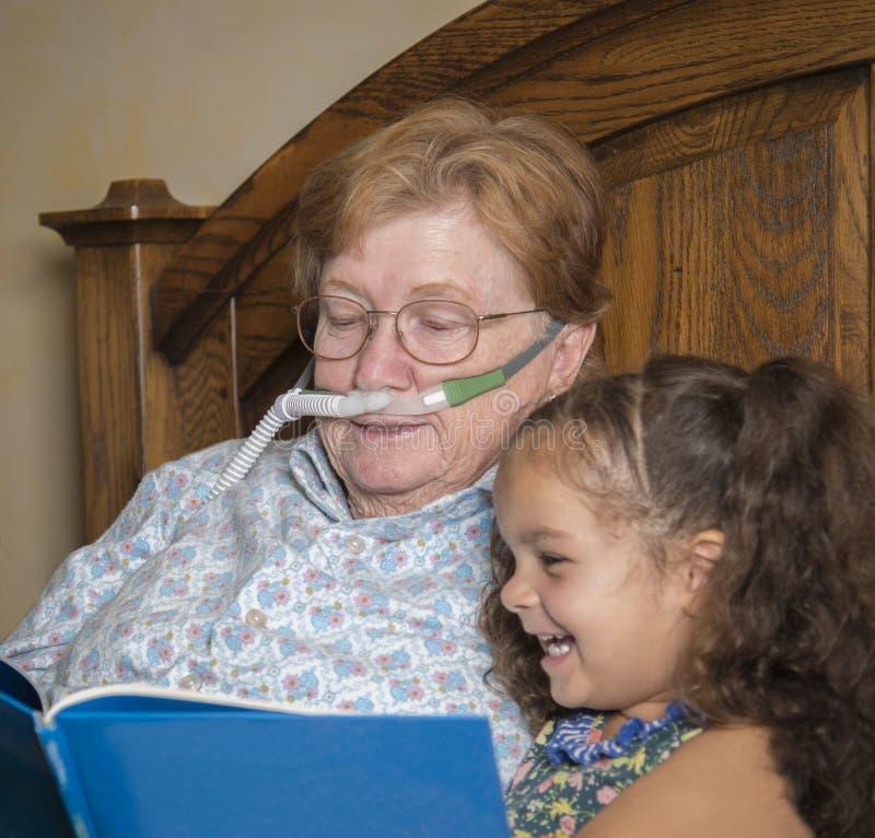 Η γυναίκα που φορά το οξυγόνο διαβάζει στο μικρό κορίτσι στοκ φωτογραφία με δικαίωμα ελεύθερης χρήσης