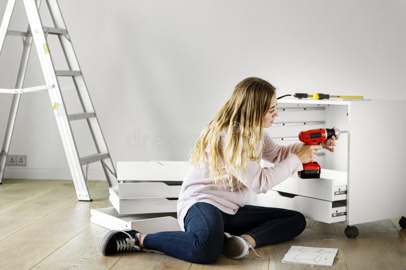Η γυναίκα που χρησιμοποιεί το ηλεκτρονικό τρυπάνι εγκαθιστά το γραφείο στοκ εικόνα με δικαίωμα ελεύθερης χρήσης