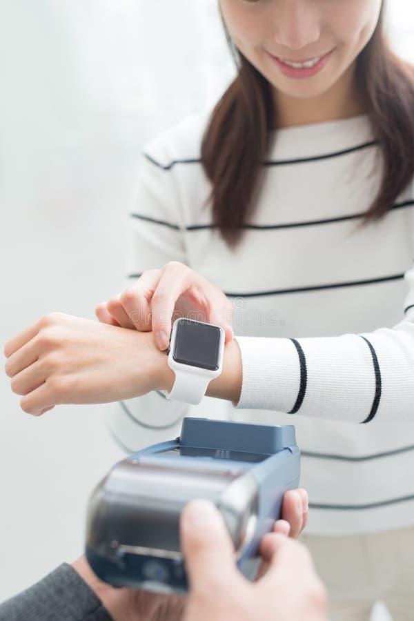 Η γυναίκα πληρώνει από το έξυπνο ρολόι στοκ φωτογραφία
