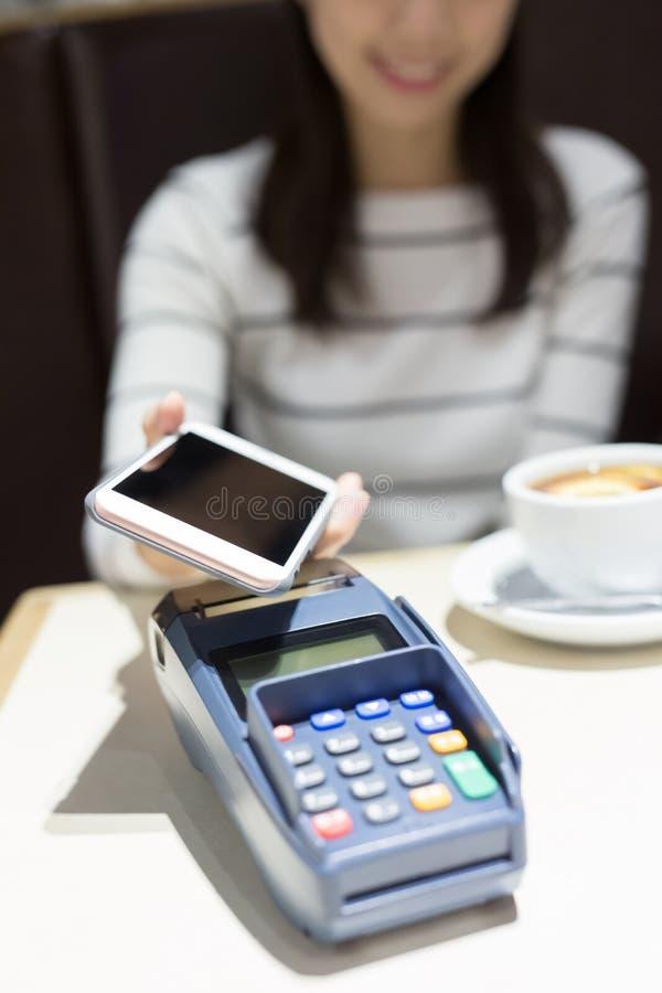 Η γυναίκα πληρώνει με έξυπνο τηλέφωνο στοκ εικόνες