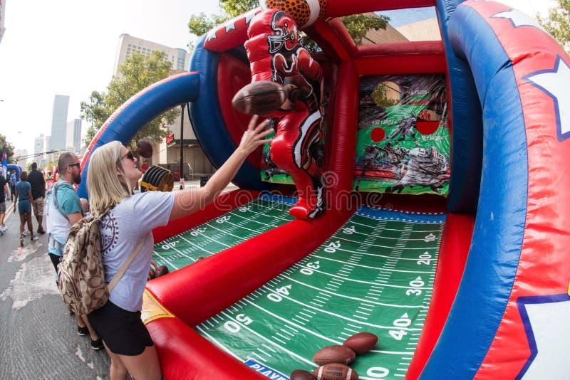 Η γυναίκα ρίχνει τα ποδόσφαιρα προς τους στόχους στο φεστιβάλ οπαδών ποδοσφαίρου κολλεγίου στοκ φωτογραφία