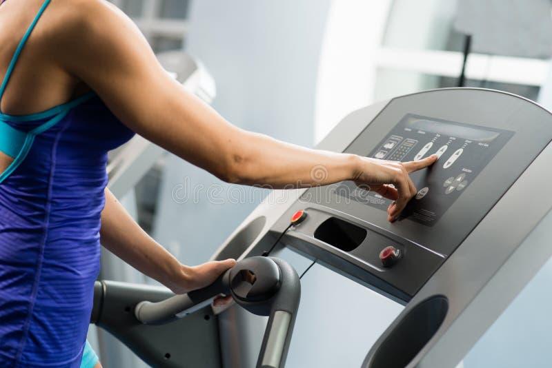 Η γυναίκα ρυθμίζει treadmill στοκ φωτογραφία