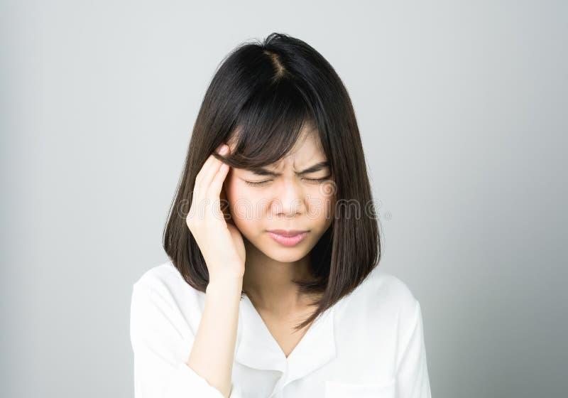 Η γυναίκα σε ένα άσπρο φόρεμα αγγίζει το κεφάλι για να παρουσιάσει πονοκέφαλό της Οι αιτίες μπορούν να προκληθούν από την πίεση ή στοκ φωτογραφία