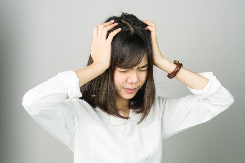Η γυναίκα σε ένα άσπρο φόρεμα αγγίζει το κεφάλι για να παρουσιάσει πονοκέφαλό της Οι αιτίες μπορούν να προκληθούν από την πίεση ή στοκ εικόνες