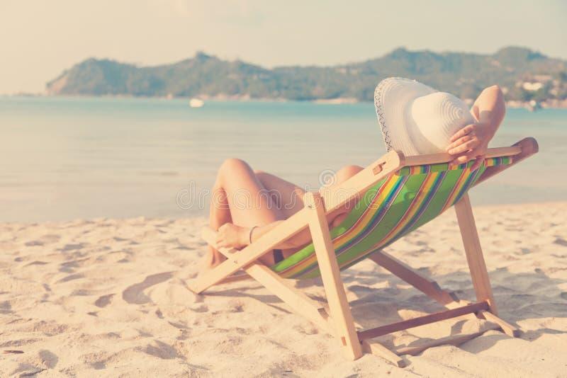 Η γυναίκα σε ένα καπέλο σε μια παραλία, που κάθεται σε μια γέφυρα προεδρεύει και που προσέχει στοκ φωτογραφία με δικαίωμα ελεύθερης χρήσης