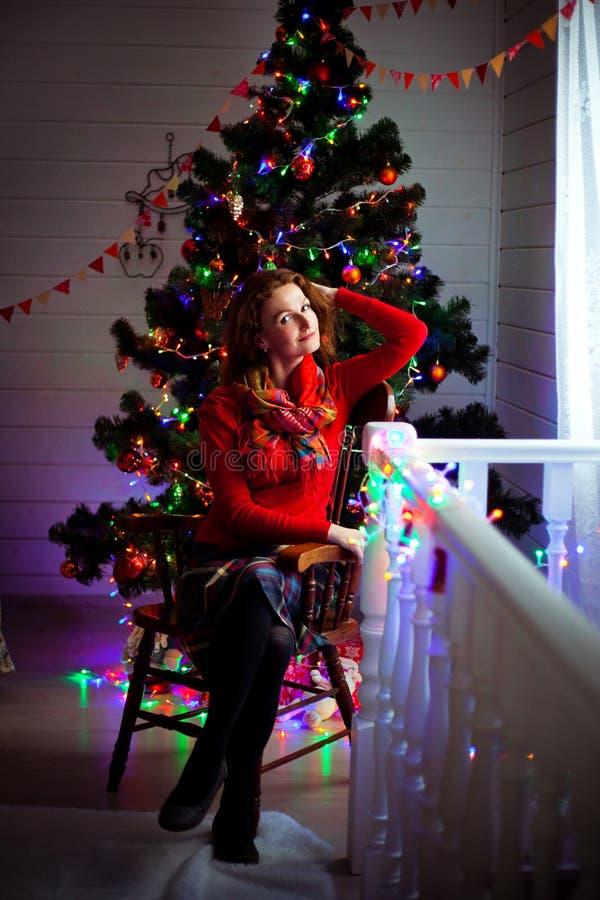 Η γυναίκα σε ένα κόκκινο πουλόβερ κάθεται στην καρέκλα σε ένα υπόβαθρο του χριστουγεννιάτικου δέντρου με τα φω'τα και το διακοσμη στοκ φωτογραφίες