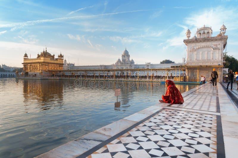 Η γυναίκα σε ένα κόκκινο saree κάθεται και προσεύχεται στο χρυσό ναό στα ξημερώματα _ Ινδία στοκ φωτογραφία