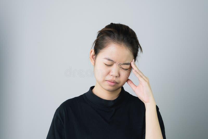 Η γυναίκα σε ένα μαύρο φόρεμα αγγίζει το κεφάλι για να παρουσιάσει πονοκέφαλό της Οι αιτίες μπορούν να προκληθούν από την πίεση ή στοκ εικόνα με δικαίωμα ελεύθερης χρήσης