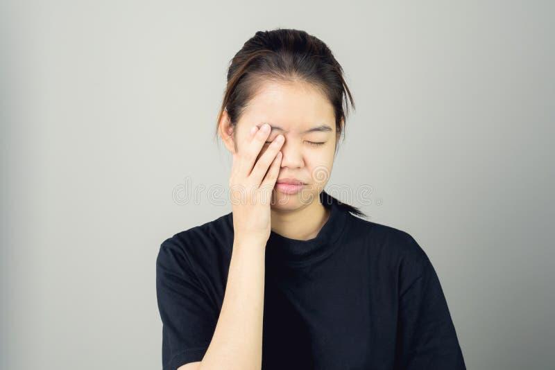 Η γυναίκα σε ένα μαύρο φόρεμα αγγίζει το κεφάλι για να παρουσιάσει πονοκέφαλό της Οι αιτίες μπορούν να προκληθούν από την πίεση ή στοκ φωτογραφία