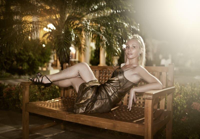 η γυναίκα σε ένα φόρεμα βραδιού βρίσκεται σε έναν πάγκο κάτω από έναν φοίνικα τη νύχτα στοκ φωτογραφία με δικαίωμα ελεύθερης χρήσης