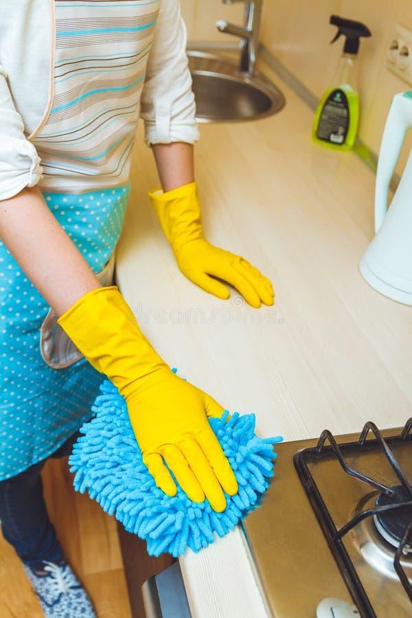 Η γυναίκα σε μια ποδιά κάνει τον καθαρισμό στοκ εικόνες