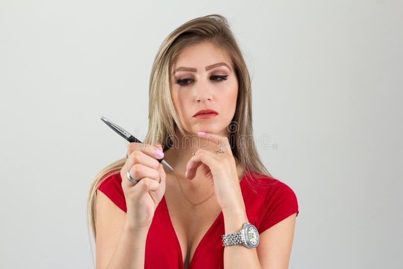 Η γυναίκα σκέφτεται για αυτά που να γράψουν σχίσιμο Ξανθό πρόσωπο α στοκ φωτογραφία με δικαίωμα ελεύθερης χρήσης