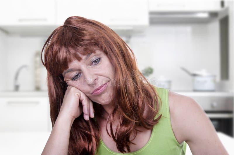 Η γυναίκα σκέφτεται στην κουζίνα της στοκ εικόνες