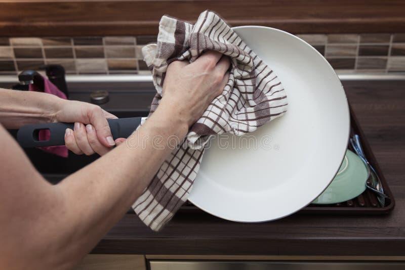 Η γυναίκα σκουπίζει τα πιάτα στην κουζίνα στοκ εικόνες